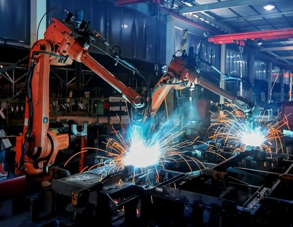 Large factory robotic arms are spraying sparks to weld car frames