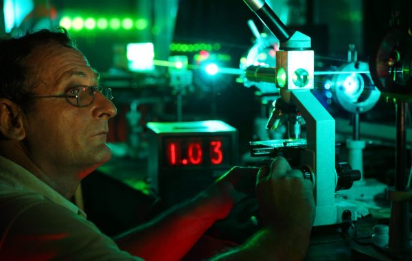 Scientist with glass demonstrate laser of microparticles near timer