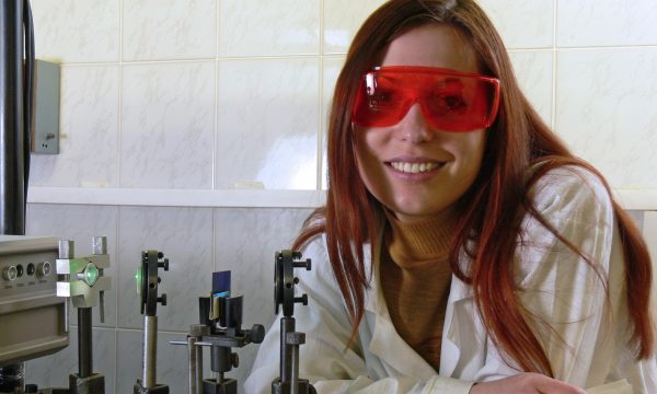 The young nice woman-scietist is standing near the stand with laser.